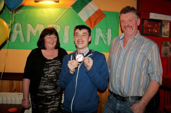 "Hugely popular Hero, World Olympic Champion, Brendan O'Sullivan pictured with his very happy parents, Margaret and Tom of Rathduane in the parish of Millstreet.   How very proud Brendan's parents must be of a son who so magnificently represented Ireland at world level gaining a highly prestigious World Olympic Medal in Floorball - a sport which only featured at world level for the very first time in Korea.   Below we view just some of the great gathering of relatives, friends and supporters who truly surprised Brendan when he arrived at the Bush Bar at 9.45 pm.   We've lots more pictures to feature later.  We thank Humphrey Hickey (of the ""Bush Bar"") for alerting us in time to meet with Brendan.   We also recorded an interview with the World Olympic Hero for later transmission on LTV2.  (S.R.)"