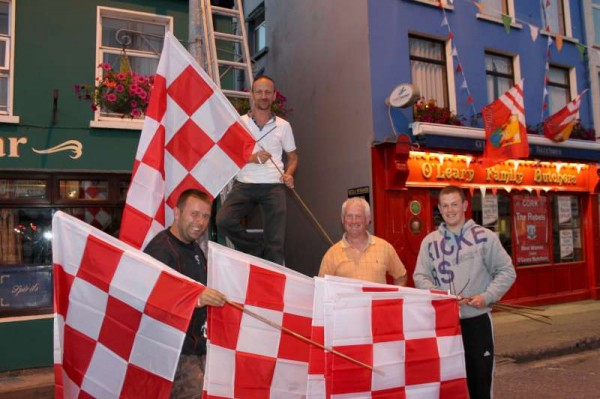 From left - Jeremiah Keating, Tony McCaul, Denis and Eric Hickey superbly arrange a wonderful Cork colours display of several flags at The Square,Millstreet on Tuesday night (3rd Sept. 2013). It was Deputy Áine Collins, T.D. who sponsored this very impressive feature in support of Cork in next Sunday's All-Ireland Hurling Final in Croke Park.   Denis's encouragement to celebrate the occasion especially as Mark Ellis is on the Cork Team - is certainly gaining momentum as we note an increasing number of new displays appearing. Click on the images to enlarge.   (S.R.)