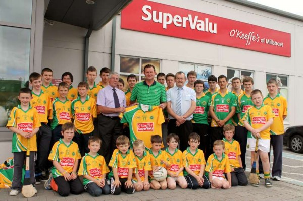 Five magnificent sets of very impressive Jerseys were magnanimously presented to Millstreet Juvenile G.A.A. Club at an uplifting occasion outside the Minor Row Supermarket on Saturday afternoon (31st August 2013).  From left:  Tommy Burke, G.A.A. and Supervalu Legend presenting Tom Flahive (Musician supreme) of Millstreet G.A.A. Juvenile Club with the Jerseys.  Also included - Joe Fitzgerald, Manager O'Keeffe's Supervalu, Millstreet and main Coordinator of the very important occasion.  (S.R.)