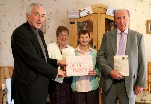 Canon John Fitzgerald, P.P., Millstreet presents the President's Cheque to the wonderful one hundred years young, Julia Murphy, Gortavehy, Millstreet.   Also included in the historic picture taken in Julia's very welcoming home is her son, Donie and Winnie O'Connor.  Click on the picture to enlarge.  (S.R.)