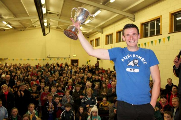 Team Captain, Michael Vaughan raises the very impressive Cup for the capacity audience in Millstreet  GAA Community Hall.