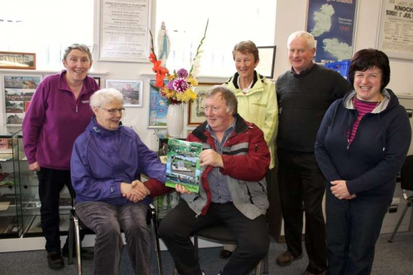 "Bridget King presents a copy of the excellent ""Down the Lawn"" to Michael Kelleher (home on holiday from Australia) at Millstreet Museum on Thursday, 16th October.  Also present from left - Mary Kelleher, Kit O'Sullivan, Denis Hickey and Mary Cronin.  Click on the image to enlarge.  (S.R.)"