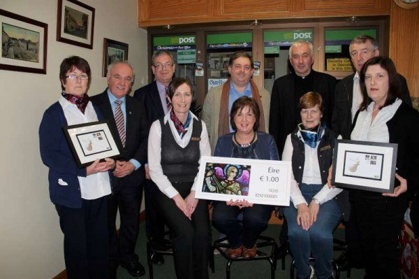 Official Launch of the Millstreet Christmas Stamp at Millstreet Post Office on Monday, 1st December.  Included are the Staff of Millstreet Post Office, from left: Anne, Margaret, Patricia and Noreen.  Standing from left Seán (Museum), Frank (An Post, Cork),  Bill (photographer of stained glass window which appears on the stamp), Canon John,Donal (who recently retired from Cork G.P.O.) and Julie (Sacristan).  More pictures to follow later.  Click on the image to enlarge.  (S.R.)