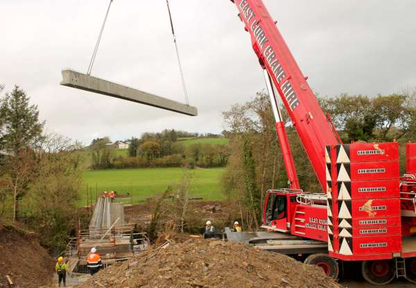 "The lowering in place of the final beam at Tuesday morning's historic developement at the Boeing Crossing in Dooneen, Millstreet. The new ""Áth an Mhuilinn"" Walk Bridge which is a very important addition to the national Beara-Breifni Walkway is a dream come true for the Organising Committee. The official opening and access to the public is still quite some time away. This will be officially announced when this truly superb construction is fully completed."