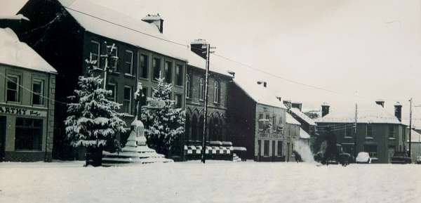 "We thank Jerry Lehane for these two wonderful images of a snowy Square in the Millstreet of the 1960s or 1970s.  We've been trying to read the Posters on the window of McCarthy's Bar - One reads ""Whist Drive"".  And note the VW car outside the Jeweller's Shop.   The petrol pumps outside Lucey's Garage are also visible.   We welcome the suggestions as to what Christmas it is exactly.  Our Museum is being officially reopened on this Wednesday, 14th Oct. at 7pm.  Click on the images to enlarge.  (S.R.)"
