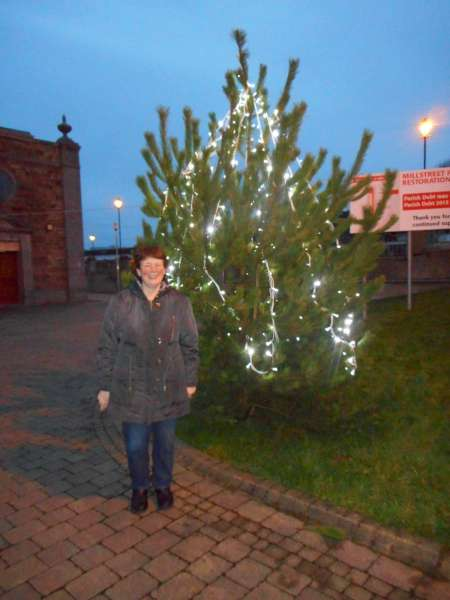 Helen Murphy pictured beside the outdoor Christmas Tree near St. Patrick's Church, Millstreet. Click on the image to enlarge. (S.R.)